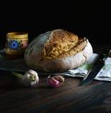 Свежий хлеб пшеницы, чеснок, деревянный шейкер соли с солью, полотенце хлопка, нож Весь это лежит на темном деревянном столе Smel стоковая фотография rf