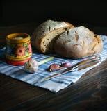 Свежий хлеб пшеницы, чеснок, деревянный шейкер соли с солью, полотенце хлопка, нож Весь это лежит на темном деревянном столе Smel стоковые изображения