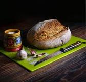 Свежий хлеб пшеницы, чеснок, деревянный шейкер соли с солью, полотенце хлопка, нож Весь это лежит на темном деревянном столе Smel стоковое фото