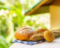 Свежий хлеб и checkered салфетка на деревянной таблице на сельском backgr Стоковая Фотография