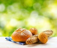 Свежий хлеб и checkered салфетка на деревянной таблице на сельском backgr Стоковые Изображения RF