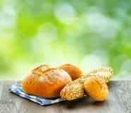Свежий хлеб и checkered салфетка на деревянной таблице на сельском backgr Стоковое фото RF