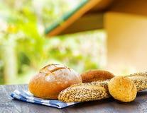 Свежий хлеб и checkered салфетка на деревянном столе на сельском backgr Стоковая Фотография