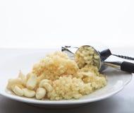 Свежий чеснок задавленный дробилкой чеснока на белом блюде на кухне Стоковые Изображения