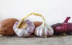 Свежий чеснок, красные луки и картошки Овощи на светлой предпосылке стоковое фото rf