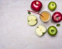 Свежий яблочный сок, отрезанные яблоки различных разнообразий, с стеклом сока cl взгляд сверху предпосылки соломы деревянный дере Стоковое Фото