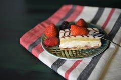 Свежий cream торт куска с клубниками вилки на черноте Стоковая Фотография