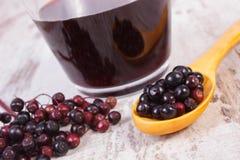 Свежий elderberry с деревянными ложкой и соком на старой доске, здоровом питании Стоковое Изображение RF