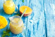 Свежий smoothie манго в 2 стеклах с плодоовощами на предпосылке голубого torquise деревянной деревенской с космосом экземпляра Стоковое Изображение