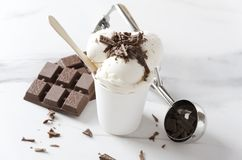 Свежий sundae мороженого с шоколадом брызгает на ложке верхней части, шоколадного батончика и мороженого на белой таблице, взгляд стоковые фотографии rf