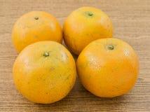 4 свежих апельсина на деревянной доске Стоковые Изображения