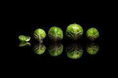 4 свежих зеленых ростка Брюсселя в строке изолированной на черном backg Стоковое Изображение