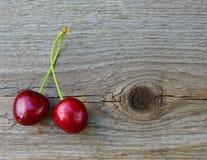 2 свежих зрелых красных сладостных вишни на деревянной предпосылке Стоковые Изображения
