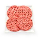 4 свежих куска гамбургера на белой плите Стоковые Изображения RF