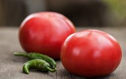 2 свежих доморощенных томата и пряных зеленых перцы chili на деревенском деревянном кухонном столе Стоковое Изображение
