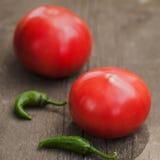 2 свежих доморощенных томата и пряных зеленых перцы chili на деревенском деревянном кухонном столе Стоковое фото RF