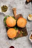 3 свежих домодельных различных гамбургера на деревянной доске Стоковое Фото