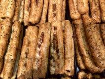 Свежо испеченные длинные плюшки с семенами сезама на витрине на пекарне стоковая фотография