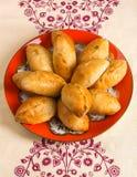 Свежо испеченные румяные пироги лежат в положении плиты на скатерти стоковые фотографии rf