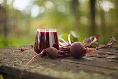 Свекловичный сок в стекле на таблице Стоковое Фото