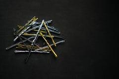 Сверкная золото металла серебряное и черные hairpins на черном backgr Стоковое фото RF
