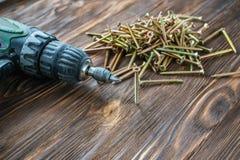 Сверло, винты и шпонки на деревянной предпосылке стоковые изображения rf