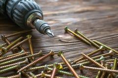 Сверло, винты и шпонки на деревянной предпосылке стоковые изображения