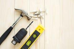 Сверло и молоток, уровни и винт на деревянной предпосылке для DIY Стоковое фото RF