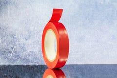 Сверните красную электрическую ленту на серой предпосылке стоковое фото rf