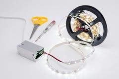 Сверните спиралью светящие свет прокладки СИД и трансформатор напряжения тока стоковая фотография rf