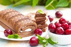 Сверните с шоколадом, сладостной сливк и вишнями стоковая фотография