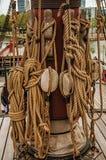 Свернутая веревочка и шкивы поддержанные на центральном рангоуте парусного судна на пасмурный день в Амстердаме стоковые изображения
