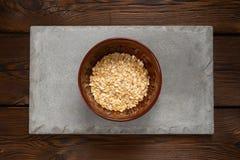 Свернутые овсы в коричневом шаре на конкретной плитке на деревянной предпосылке стоковые изображения rf