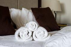 Свернутые полотенца на кровати Стоковая Фотография RF