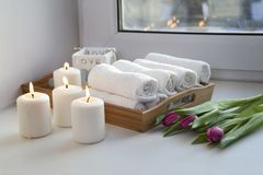 Свернутые полотенца руки на подносе рядом с освещенными свечами и букете тюльпанов в салоне курорта Стоковые Изображения