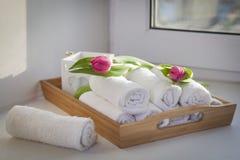Свернутые полотенца руки на подносе рядом с освещенными свечами и букете тюльпанов в салоне курорта Стоковое Изображение