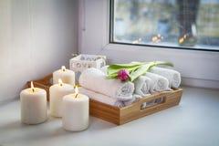 Свернутые полотенца руки на подносе рядом с освещенными свечами и букете тюльпанов в салоне курорта Стоковая Фотография RF