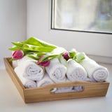 Свернутые полотенца руки на подносе рядом с освещенными свечами и букете тюльпанов в салоне курорта Стоковые Фото
