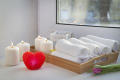 Свернутые полотенца руки на подносе рядом с освещенными свечами и букете тюльпанов в салоне курорта Стоковые Изображения RF