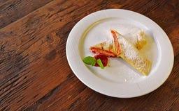 Свернутые crepes с красным вареньем на деревянной предпосылке Стоковое Изображение