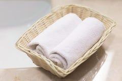 2 свернули белые полотенца руки в светлой прямоугольной корзине на Стоковая Фотография