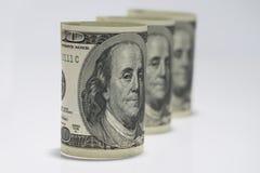 3 свернули вверх по 100 долларовым банкнотам на белой предпосылке Стоковое Изображение RF