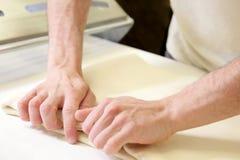 Свертывать вне тесто мужскими руками на хлебопекарне Стоковое фото RF