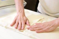 Свертывать вне тесто мужскими руками на хлебопекарне Стоковые Фотографии RF