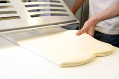 Свертывать вне тесто мужскими руками на хлебопекарне Стоковое Фото