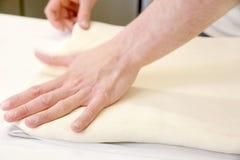 Свертывать вне тесто мужскими руками на хлебопекарне Стоковая Фотография