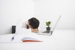 Сверх-работаемый средний взрослый бизнесмен спать компьтер-книжкой на столе Стоковое Изображение