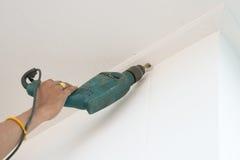 Сверлить потолок с электрическим сверлильным аппаратом стоковая фотография