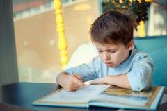 Сверлильная и утомленная книга чтения мальчика Стоковая Фотография RF