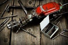 Сверло с сверлами на деревянной предпосылке Стоковые Изображения RF